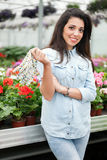 Young smiling woman florist working in the greenhouse Stock Photography