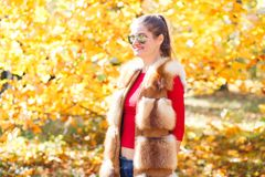 Young woman in fur vest posing in autumn park Royalty Free Stock Photos