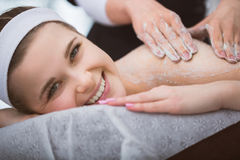 Young smiling woman getting firming sugar scrub therapy on her b Royalty Free Stock Photo