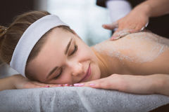 Young smiling woman getting firming sugar scrub therapy on her b Stock Photos