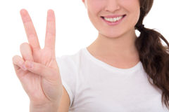 Young smiling woman giving peace sign isolated on white Stock Image