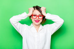 Young smiling woman in glasses. Portrait of beautiful smiling young woman in glasses on the wonderful studio green background Stock Photography