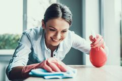 Young Smiling Woman in Gloves Cleaning House. Happy Beautiful Girl wearing Protective Gloves Cleaning Desk by spraying Cleaning Products and wiping with Sponge royalty free stock photos