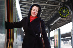 Young smiling woman going to enter a train. Stock Image