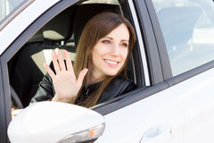 Young smiling woman greeting with hand from car. Stock Images
