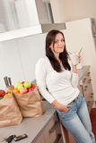 Young smiling woman with groceries in the kitchen Royalty Free Stock Photos