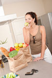 Young smiling woman with groceries in the kitchen Stock Photo