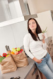 Young smiling woman with groceries in the kitchen Stock Photos