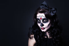 Young smiling woman with Halloween skull make up over black and Royalty Free Stock Image