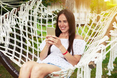 Young smiling woman in hammock in sunny garden Stock Image
