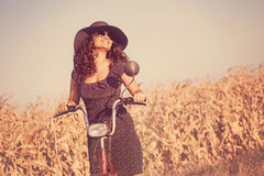 Young smiling woman with hat and sunglasses, on scooter Royalty Free Stock Photos