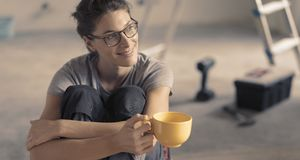Woman doing a home renovation and having a coffee break stock image