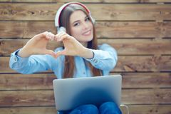 Young smiling woman with headphones makes heart shape with hands sitting on the background of wall of wooden boards royalty free stock image
