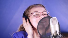 A young smiling woman in headphones singing song in the studio. Mid shot
