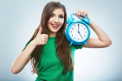Young smiling woman hold watch. Beautiful smiling girl portrait. Studio background female model royalty free stock photos