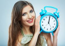 Young smiling woman hold watch. Beautiful smiling girl portrait. Isolated studio background female model royalty free stock image