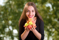 Young and smiling woman holding a bunch of colorful macaroons on Royalty Free Stock Photography