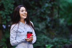 Young smiling woman holding the cup of coffee. Young smiling brunette woman, wearing blue denim shirt and holding the red cup of coffee royalty free stock image