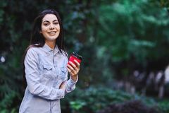 Young smiling woman holding the cup of coffee. Young smiling brunette woman, wearing blue denim shirt and holding the red cup of coffee stock images
