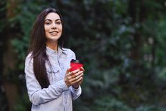 Young smiling woman holding the cup of coffee. Young smiling brunette woman, wearing blue denim shirt and holding the red cup of coffee stock photos