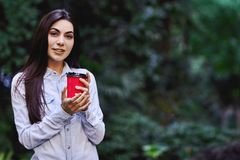 Young smiling woman holding the cup of coffee. Young smiling brunette woman, wearing blue denim shirt and holding the red cup of coffee stock image