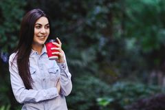 Young smiling woman holding the cup of coffee. Young smiling brunette woman, wearing blue denim shirt and holding the red cup of coffee royalty free stock photography