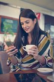 Young smiling woman holding a cup of coffee and text messages. Smiling woman Stock Image