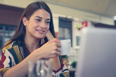 Young smiling woman holding a cup of coffee and watching somethi. Ng on laptop Royalty Free Stock Photography
