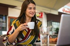 Young smiling woman holding a cup of coffee and watching somethi. Ng on laptop Royalty Free Stock Images
