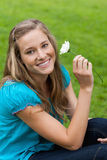Young smiling woman holding a flower. While sitting down Royalty Free Stock Image