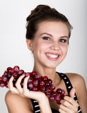 Young smiling woman holding fresh red bunch of grapes. Young smiling woman holding fresh red bunch of grapes royalty free stock images