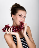 Young smiling woman holding fresh red bunch of grapes. Young smiling woman holding fresh red bunch of grapes royalty free stock image