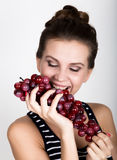 Young smiling woman holding fresh red bunch of grapes. Stock Image