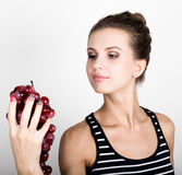 Young smiling woman holding fresh red bunch of grapes. Stock Photos