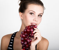 Young smiling woman holding fresh red bunch of grapes. Young smiling woman holding fresh red bunch of grapes royalty free stock photo