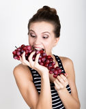 Young smiling woman holding fresh red bunch of grapes. Stock Photo