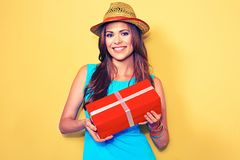 Young smiling woman holding gift box standing against yellow Stock Photos