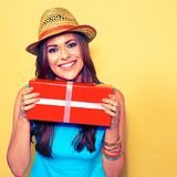 Young smiling woman holding gift box standing against yellow Stock Photo