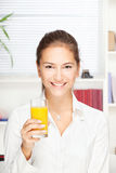 Young smiling woman holding glass of orange juice Stock Image