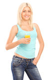Young smiling woman holding a glass of orange juice Royalty Free Stock Photography
