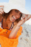 Young smiling woman holding her hat brim while lying down. Young woman holding her hat brim while lying on a beach towel and smiling stock image