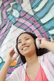 Young smiling woman holding her headphones while enjoying listening to music in front of wall with graffiti Royalty Free Stock Image