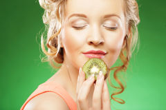 Young smiling woman holding kiwi. Royalty Free Stock Photos