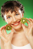 Young smiling woman holding kiwi. Stock Photography