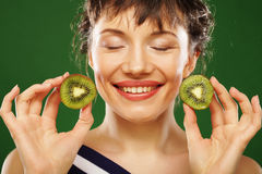 Young smiling woman holding kiwi. Royalty Free Stock Photography