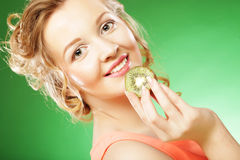 Young smiling woman holding kiwi. Royalty Free Stock Images