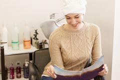 Young smiling woman holding magazine in hairdresser`s chair. Daily beauty concept Royalty Free Stock Photos