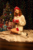 Young smiling woman holding red christmas gift. Young happy smiling casual woman holding red gift over christmas tree and lights on background. shallow depth of Royalty Free Stock Photography