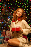 Young smiling woman holding red christmas gift. Young happy smiling casual woman holding red gift over christmas tree and lights on background. shallow depth of stock image