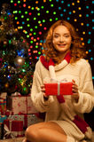 Young smiling woman holding red christmas gift. Young happy smiling casual woman holding red gift over christmas tree and lights on background. shallow depth of Stock Photos